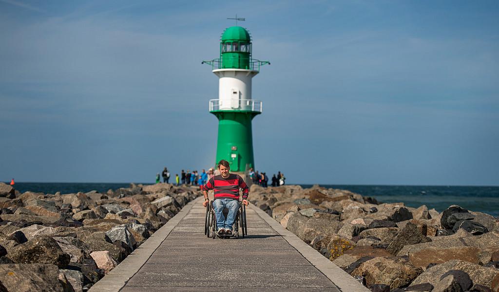 Rollstuhlfahrer an der Westmole in Warnemünde